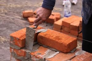 Uomo costruzione mattone parete